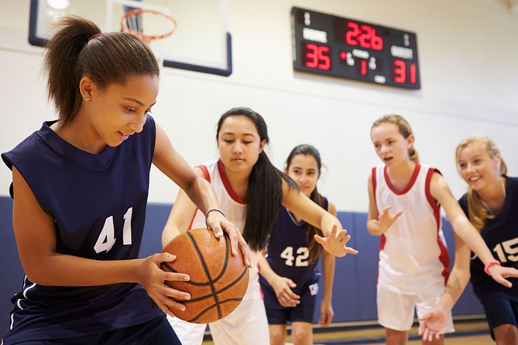 Female High School Basketball Team Playing Game In The Gym